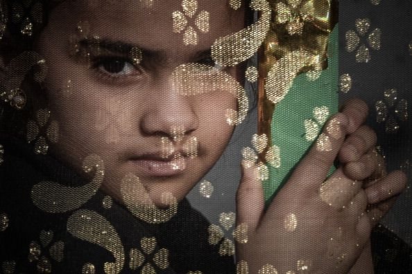 A Bahraini Shiite Muslims girl watches the Arbaeen religious festival from a window in the village of Sanabis west of Manama on January 3 2013...