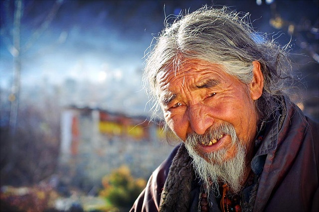Tibetan Man in Muktinath    shot with a canon d30 and a 17-35f2.8 lens. holding a white/gold reflector in my left hand to illuminate his face. this is early morning at 3800m altitude, hence the special light. muktinath is a hindu pilgrimage, in the lower mustang, just north of annapurna. this man fled from tibet with the chinese invasion to the mountains of mustang and nepal.    the white in the blurry background is snow from the annapurnas    By phitar