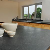 Modern kitchen with a breakfast bar that has a slate work surface, hand made in the UK by Ardosia.