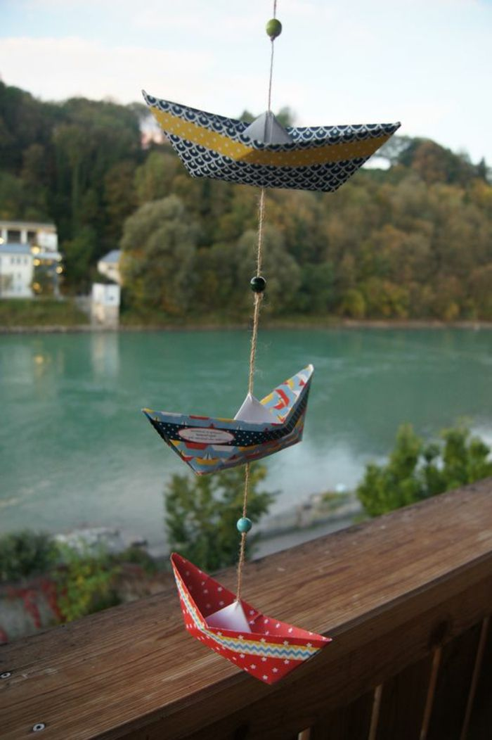 easy fun diys, three origami boats, made from multicolored patterned paper, hanging on a burlap thread, decorated with three beads