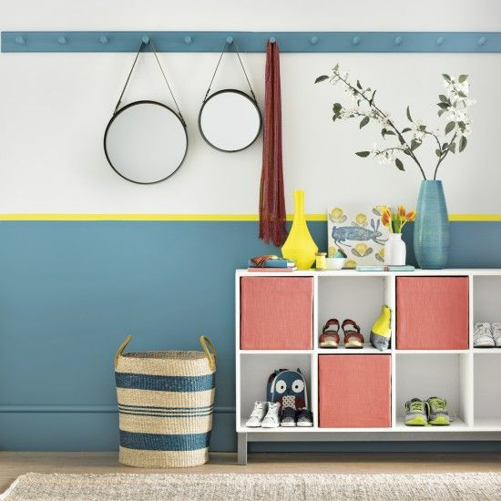 If you'd love to use bold colour but worry it will be too much, try this clever trick: paint the lower third of a wall and fake a dado rail with a thin border like this acid yellow that pops. The cheerful sideboard with juicy watermelon-coloured storage boxes makes a fabulous accent shade against the blue and yellow