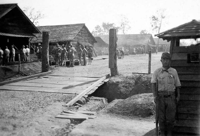 A Japanese soldier stands guard over Allied POWs at Thanbyuzayat POW camp in Burma. POWs in Thanbyuzayat were used as forced labor to build the Thai-Burma Railway. Begun in October 1942 and completed on 16 October 1943, the railway stretched 415 kilometers (257 miles) between Nong Pladuk in Thailand and Thanbyuzayat in Burma (now Myanmar). More than 60,000 Allied prisoners of war were employed in the construction of the Thai-Burma Railway