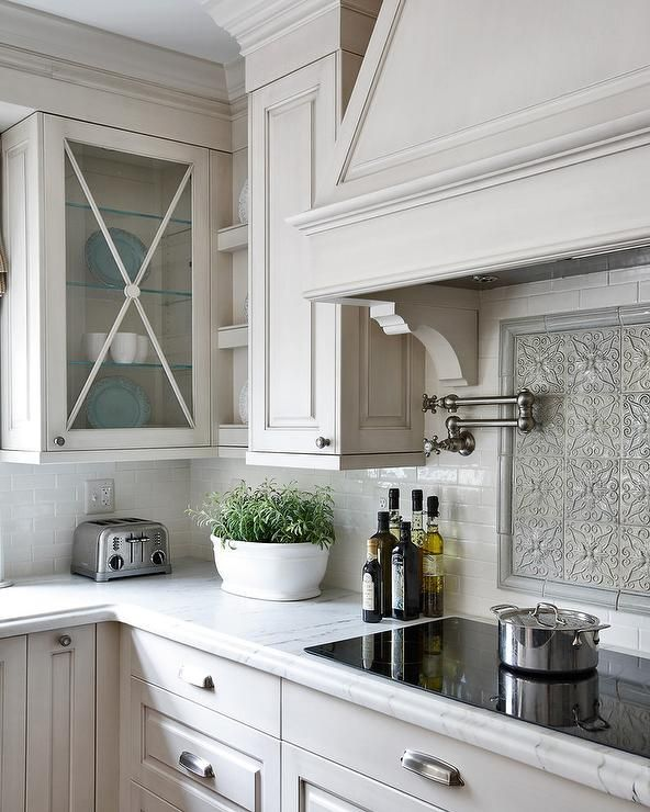 Beautiful kitchen features a gray wash cabinets paired with white marble counters and a white glazed brick tiled backsplash.