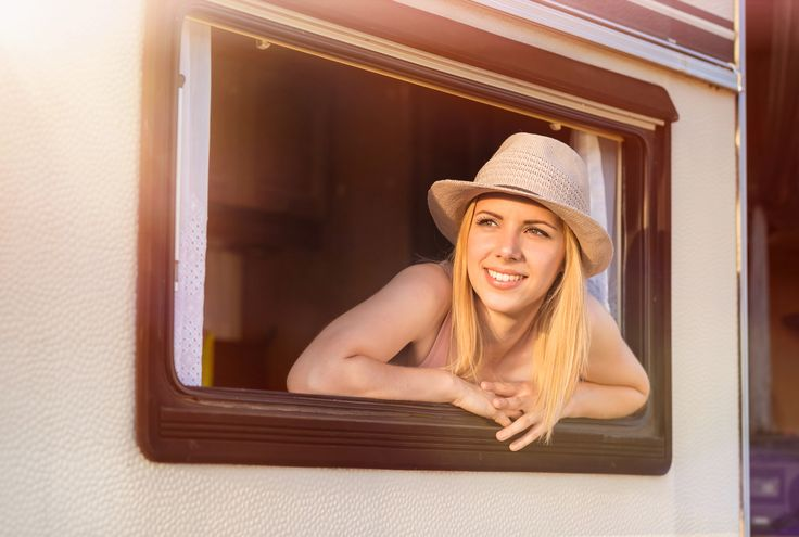 Beautiful woman in a camper van - Beautiful young woman in a camper van on a summer day