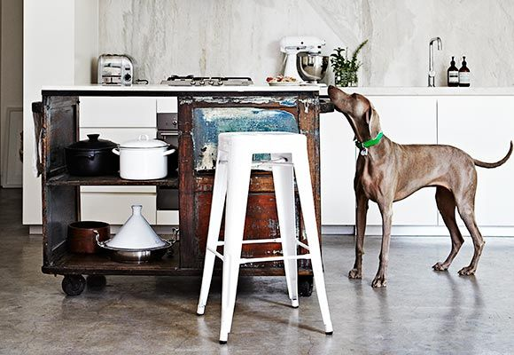 Cool eclectic. Old carpenters bench topped with marble as an island is the perfect way to add character to this otherwise neutral and moder kitchen. Great Tolix Tabouret stool too.