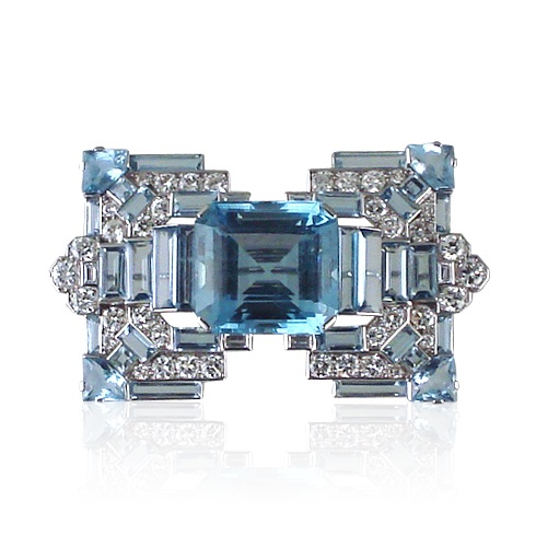 Exceptional Art Deco aquamarine and diamond  stylised buckle brooch, set to the centre with a cut-cornered rectangular aquamarine flanked by stepped and  baguette-cut aquamarine four-stone shouders to brilliant-and baguette-cut diamond mount, set to the four corners with a wedge shaped aquamarine embelllished by further baguette and square-cut aquamarines,  signed by Cartier