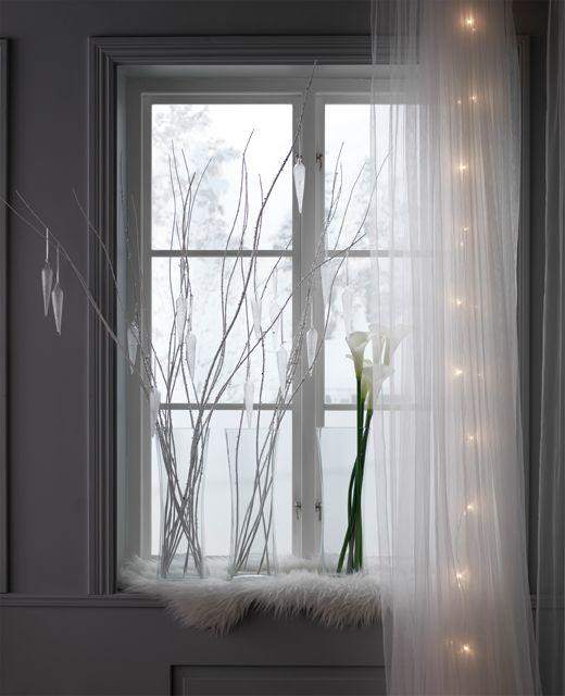 Okno so zasneženým výhľadom ozdobené sklenenými vázami, halúzkami a káliami.