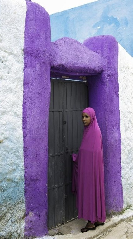 An Ethiopian woman painted her doorway purple and wears a purple hijab to celebrate Purple Hijab Day in Harar, Ethiopia. Muslim and non-Muslims around the globe observe the second Saturday in February as a time for prayer and hosting activities/workshops around the issue of domestic abuse • by Sr. Hadayai Majeed on Project Sakinah