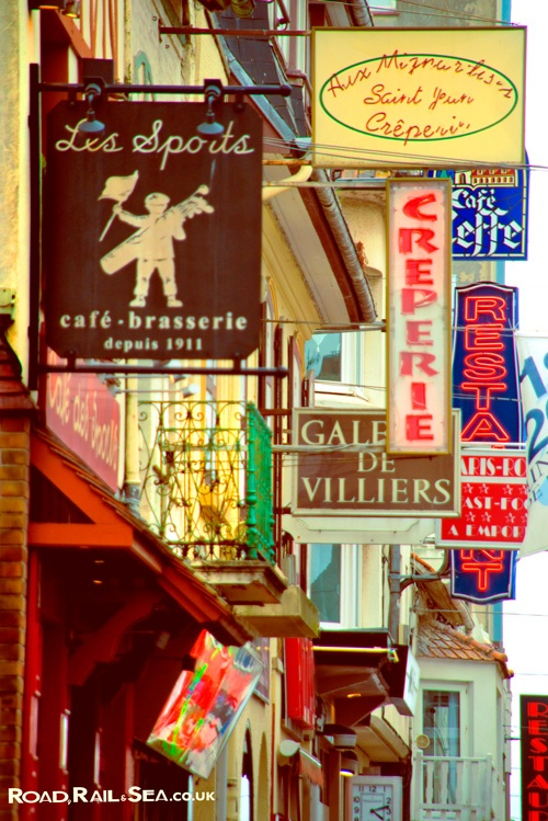 Shop and cafe signs in the town centre of Le Touquet, northern France. An original photograph by Road, Rail And Sea. If you want advice about travelling by road, rail or sea you can contact us at info at roadrailandsea dot co dot uk
