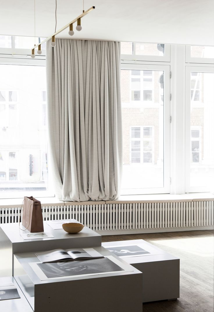 Big white curtains in an open plan gallery space, washed in natural light - Kinfolk magazine's office in Copenhagen