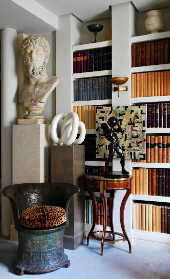Overscale sculpture on pedestals combining design eras hug sculptural bookcases filled with color coded neutral antique books striking design in living