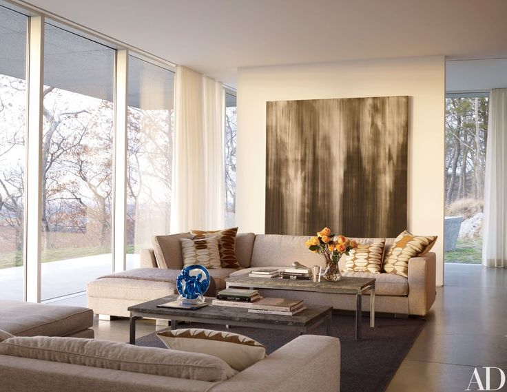 The living area's Hilton sofas by Minotti, with pillows by Judy Ross Textiles, face a pair of PK 57 cocktail tables by Poul Kjærholm, one topped with Jeff Koons's Balloon Dog porcelain plate; the painting is by Callum Innes.