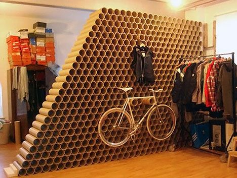 The use of these tubes (carpet roll?) is genius! I also love how it sections off the store (visable storage behind), and how is supports the hanging bike. Perfect for menswear because it's not at all feminine.