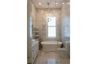 The combination of high ceilings, tiled walls, gold elements and a chandelier create a lavish atmosphere in this bathroom
