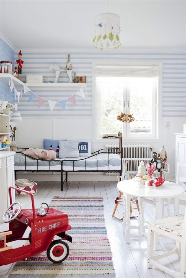 <span>Randigt på väggar och golv. Trasmatta och äldre stålsäng. Stor leksaksbil av plåt är både leksak och prydnad i rummet. <br></span>