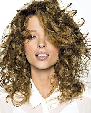 A medium blonde curly hairstyle by Saint Algue