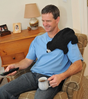 Man using Black Bear microwave heating pad to help improve flexibility in shoulder