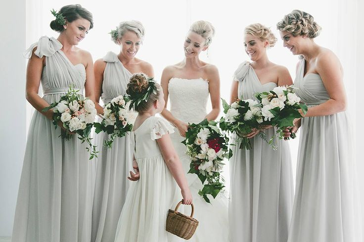 bridesmaids in grey with one shoulder tied up. Flowy dresses. Whimsical wedding bouquets