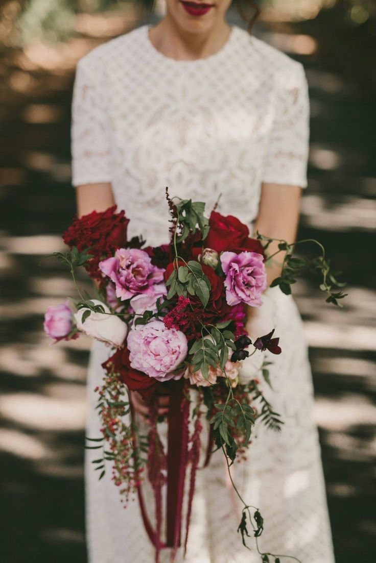 Pink, peach and plum bridal bouquet, olive leaf wedding arch and hair circlet by Shady Fig using David Austin roses, peony roses, tulips, peppercorn and amaranthus. Photographed by Zoe Morely