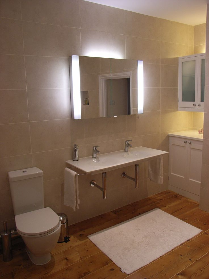 Double basin in bathroom with large mirror cabinet above. If you buy a bathroom cabinet, choose one that lights your face from the side - it's more flattering than from above. Bespoke bathroom storage also visible with built-in lights.