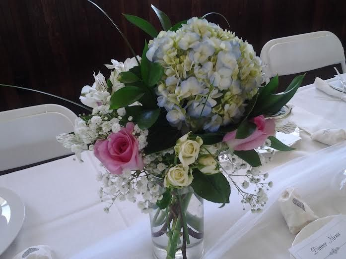 Blue Hydrangea, White Spray Roses, Pink Roses, Baby's Breathe, and Bear Grass. What a soft yet colorful centerpiece.