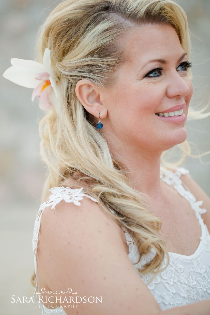 Down do bridal hairstyle, embellished with a flower. Hair & makeup by Cabo Makeyp by Alma Vallejo. Photo by Sara Richardson Photography.