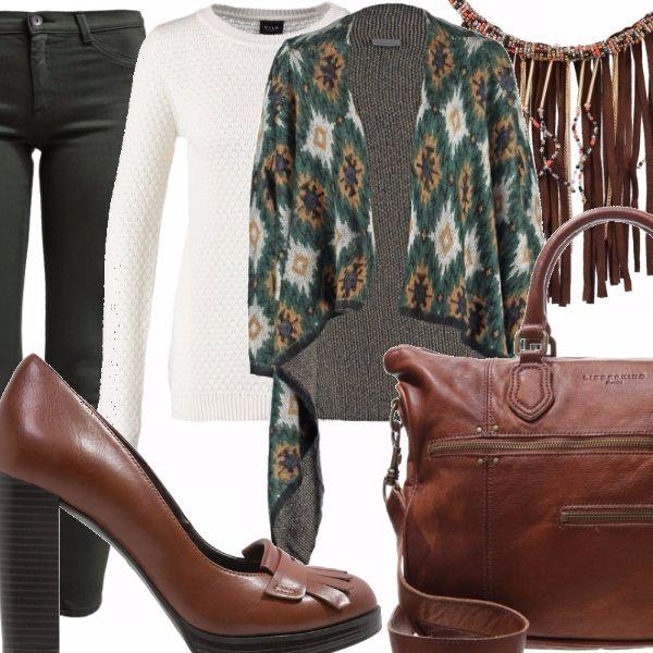 Jeans cinque tasche in denim verde scuro, maglioncino bianco a manica lunga, mantella con disegno geometrico di ispirazione etnica, collana con perline e frange, mocassino con tacco alto largo, borsa multi tasche in pelle marrone con manici e tracolla