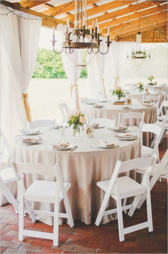 Wedding reception set up with white folding chairs, white curtains, and chandeliers