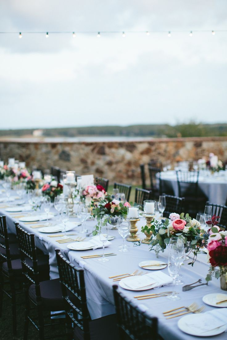 long banquet tables at this outdoor wedding reception are dressed with lush and loose arrangements of burgundy peony, pink garden roses, pink ranunculus, white spray roses, quicksand roses, blue thistle, vines and greenery on pale grey linens. a mixture of gold and silver mercury glass candleholders add the glow of candlelight.