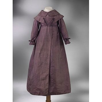 Coat dress 1820-1830 - Silk trimmed with Braid  Child's frock. Purple silk. The frock is high waisted, the bodice opens at the back, and has draw-strings at neck and waist. There is a turn-down collar, and a small cape with a stomacher point in front, decorated with braid froggings, to which a silk belt, fastening behind, is attached. The skirts are long and full, with an overlapping opening in front. the sleeves are tight, with band at wrist. White silk lining.