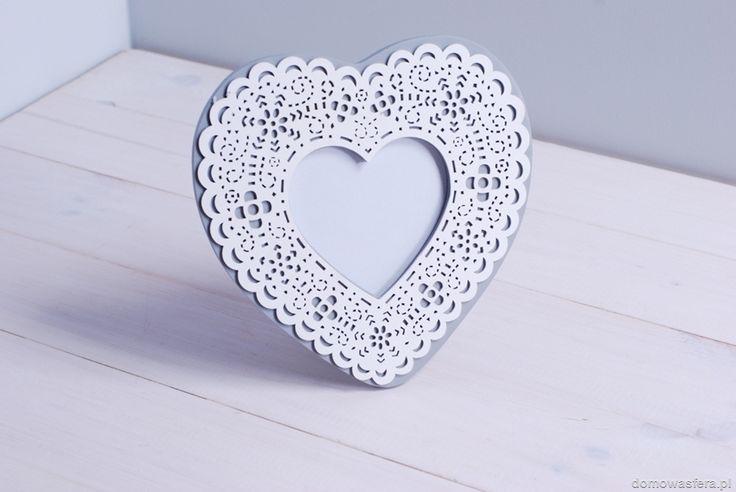 Biała ramka wykonana z drewna oraz ozdobnej warstwy perforowanej z motywem ornamentu. Ramka w kształcie serca idealna na zdjęcie bliskiej Ci osoby.
