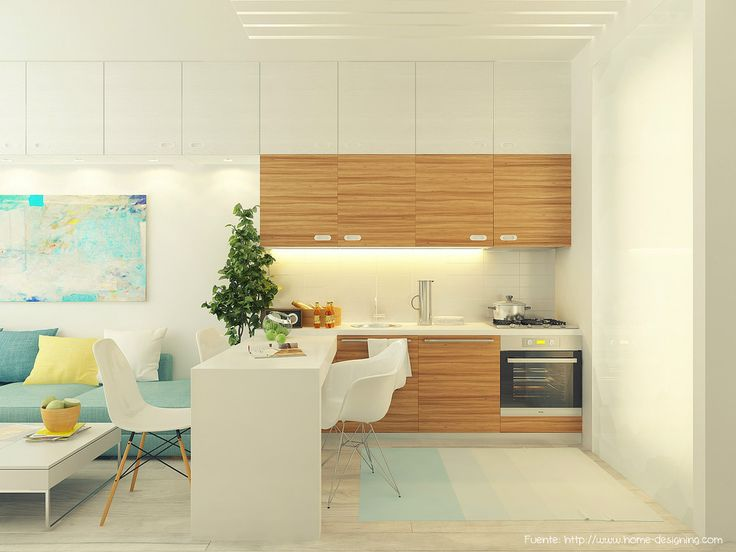 En un monoambiente de 29m2, la cocina se ubicó a lo largo, con una mesa en L para dividir. Las alacenas blancas sobrepasan el límite de la cocina, llegando hasta el otro extremo del ambiente. Al ser del mismo color que la pared, pasan desapercibidas.