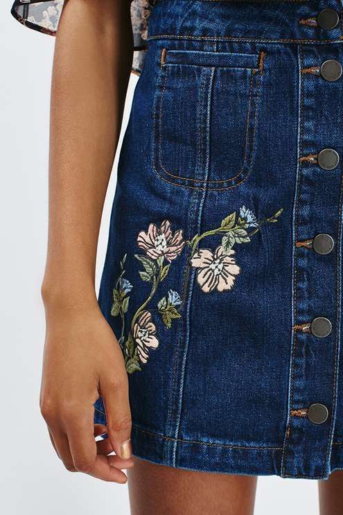 Look to pretty embroidery detailing in the MOTO denim mini skirt. Cut with a slim fitting A-line silhouette, it sits high on the waist and comes detailed with a whimsy floral embroidery. Features handy side pockets with a button down placket to fasten. #Topshop
