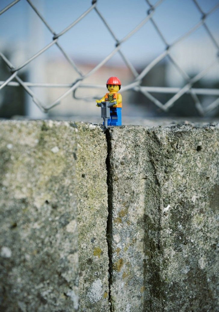 A LEGO street worker cracks the pavement in half