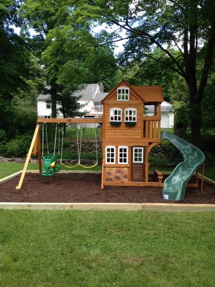mulch wood wooden playset swings plastic slide and loads of fun for