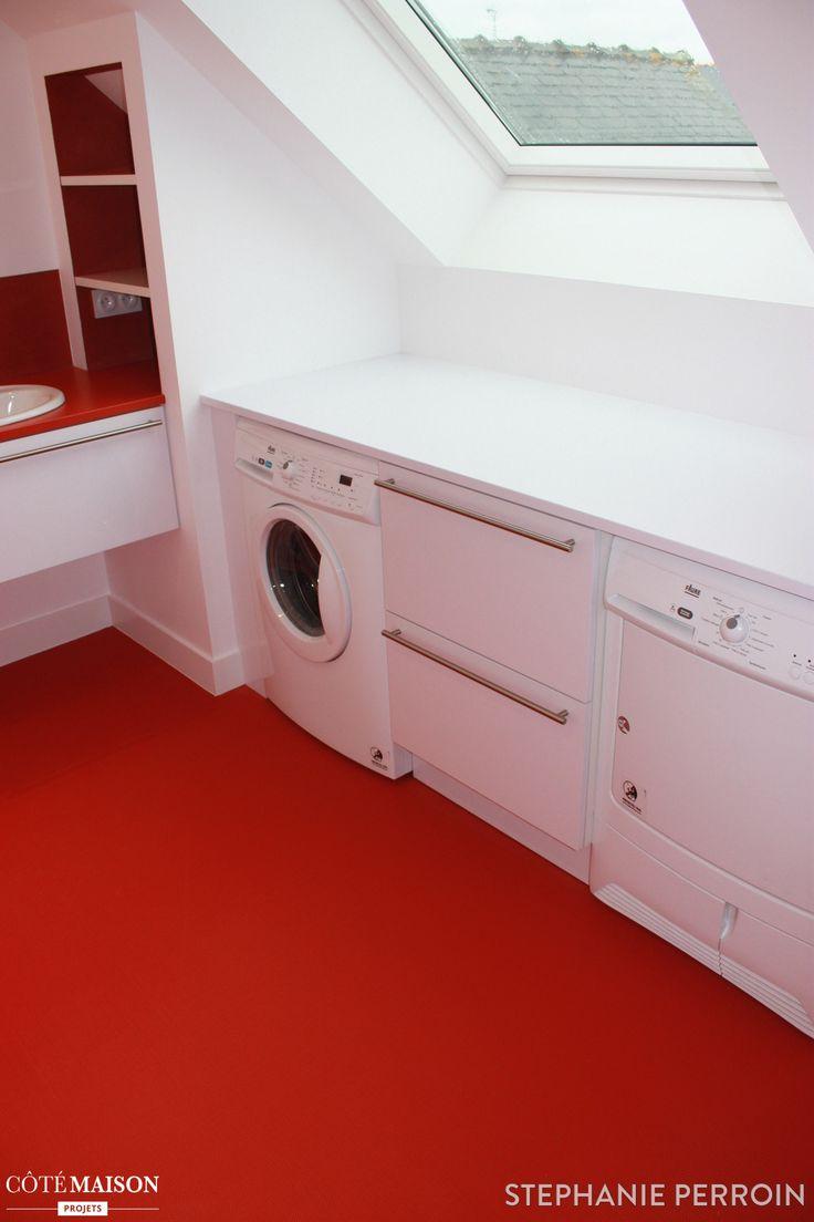 Une salle de bains sous les combles, au sol rouge brut et mobilier blanc pour un effet de contraste saisissant.