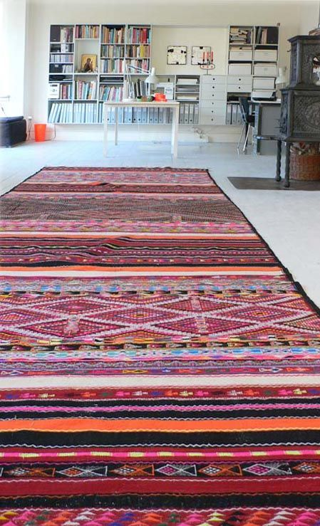 Brightly patterned Berber carpet in a mostly white Scandinavian office.