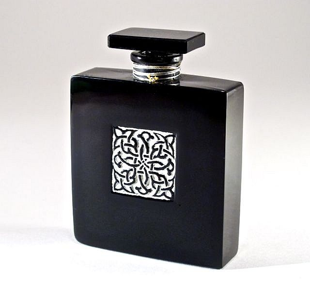 1928 Lionceau Poeme Arabe perfume bottle and stopper, black glass, ochre enamel recessed detail. 3 1/4 in.