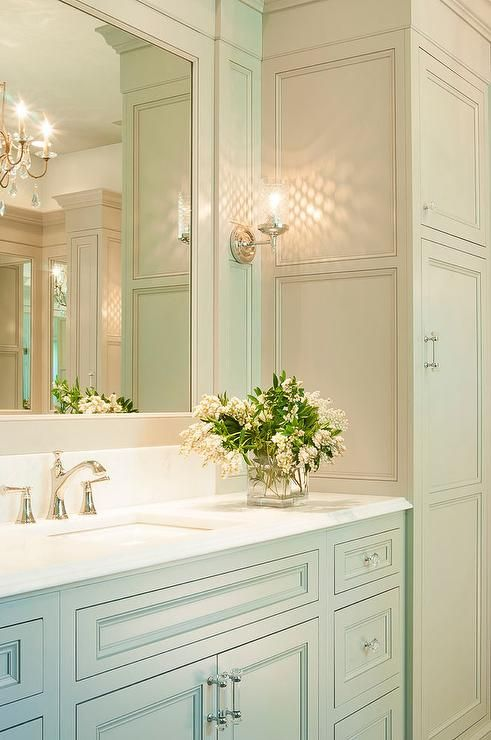Traditional gray bathroom features gray shaker vanity cabinets paired with white quartz countertops under an inset mirror lit by glass sconces flanked by tall gray linen cabinets.