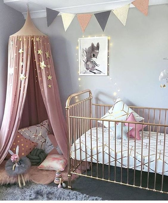 Dusty pink and grey nursery made even prettier with this string of fairy lights, bunting and copper cot. See all the stylish nurseries we've curated on the blog here >>>