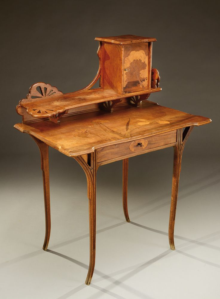 A tinted beech wood desk with an exotic wood marquetry of iris motifs and butterflies. Opening by a drawer in the middle and with storage space on the higher part. Signed «Gallé». Circa 1900.