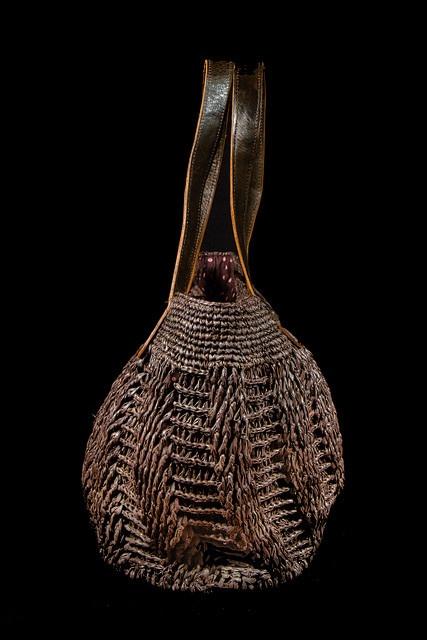 """""""City""""  Sac en raphia. Le fond et le haut du sac sont réalisés en crochet de raphia et le corps du sac en tricot de raphia. Les anses sont en cuir, et le fond extérieur du sac protégé par des boutons de coco.  Doublure intérieure munie de deux poches dont une pour téléphone.  Fermeture à glissière.  Dimensions : Longueur 50 cm x Hauteur 28 cm x Largeur 17 cm."""