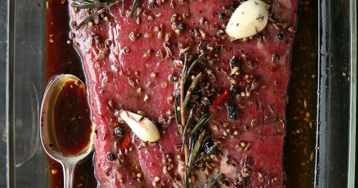 Flank steak, also known as London broil, isn't the most tender cut of beef, but it is one of the most flavorful. The key to getting a tender flank steak is to let the meat marinate for a good, long time — in this case, in a mixture of red wine, Worcestershire sauce, garlic, various spices, and fresh rosemary — and the carve it across the grain into thin slices before serving.