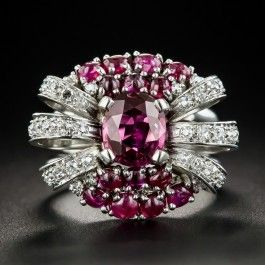 This singular, striking, and stunning cocktail ring, dating back to the 1940s, features a natural, no-heat ruby, weighing 1.38 carats. The hand fabricated platinum mounting radiates east and west with sparkling diamond-set rays, and is embellished north and south with small bright red cabochon rubies for an impressive and uniquely enchanting effect. This jubilant vintage jewel measures 7/8 by 3/4 inch.