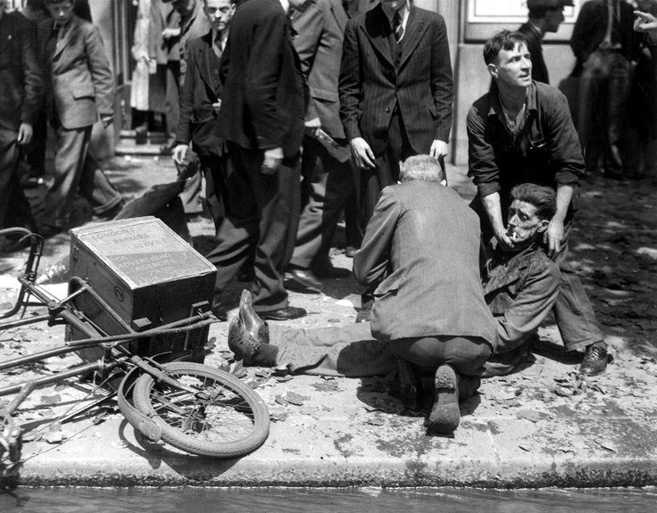 Londoners try to help victim of German aerial bombing, 1940. Note that the victim, despite his suffering, hasn't lost his cigarette from his lips.