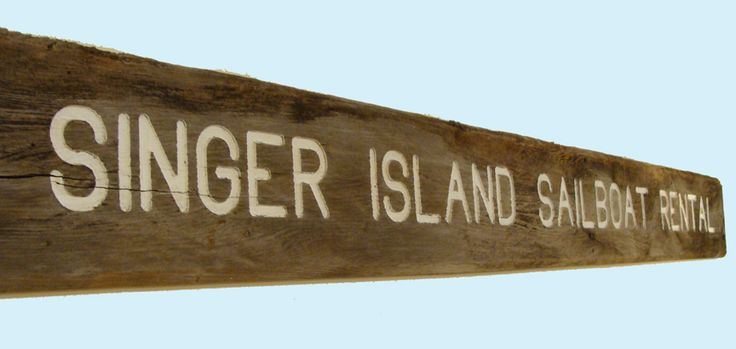"Vintage, heavily weathered outdoor nautical wood trade sign with carved letters that state ""SINGER ISLAND SAILBOAT RENTALS.""  Singer Island, Florida, Sailboat, Rental, wood, trade sign, vintage, beach, coastal"