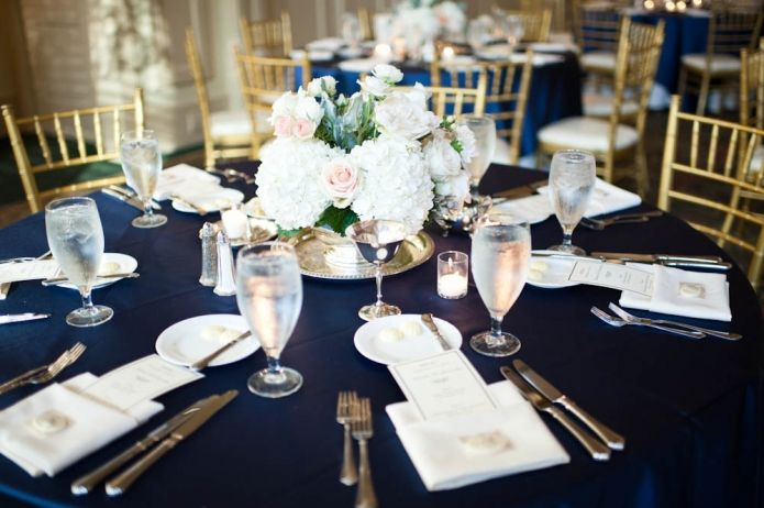 navy blue tablecloths with gold chairs and white flowers ...
