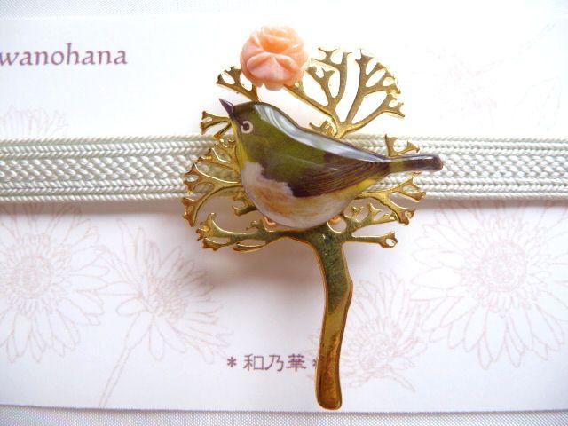 ツリーモチーフにメジロがとまる帯留めです。珊瑚細工のお花を一輪添え、早春のポエティックな雰囲気を表現してみました。 気軽な和装アクセサリーとして、お楽しみください。 【サイズ】最大幅: 約H4.7×W3.2cm 帯留め金具内径:12mm×3㎜(薄平組の三分紐) 【素材】メタルパーツ・染め珊瑚パーツ・合成樹脂・金具(金色)・他 1つ1つ、手作業で丁寧に制作しておりますので、...