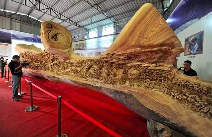 Zheng Chunhui, un célèbre sculpteur sur bois. Cette incroyable œuvre d'art est une reprise du célèbre tableau chinois, souvent surnommé la Mona Lisa chinoise, intitulé 'Le long de la rivière pendant le festival Quinming', peint par Zhang Zeduan durant la dynastie Song. . La pièce mesure 12,286 mètre de long pour 3,075 mètres de haut et 2,401 mètres de largeur.