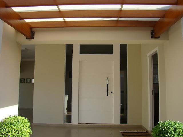 O pergolado vai do portão até a varanda. A porta , escolhemos a pivotante, com vidros laterais...clareia bem a sala.